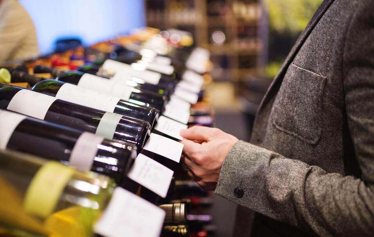 Man in a wine shop choosing a bottle of wine